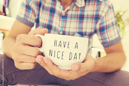Photo  young man with a cup with the text have a nice day
