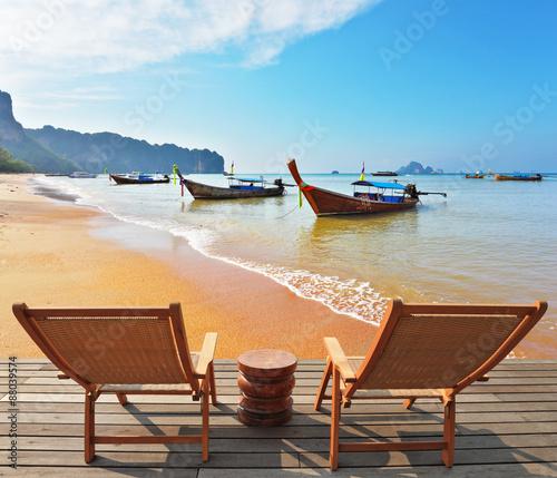 Fototapety, obrazy: Two wooden chaise lounges and  native boats