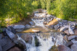 Tourist route to the Urals. Artificial waterfall in the forest with a beautiful bridge