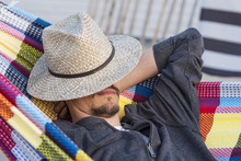 Man Relaxing In A Hammock At S...