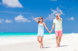 Romantic couple in bright clothes enjoying sunny day at tropical