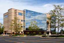Office Building – An Office Building With Glass Windows On A Sunny Day.