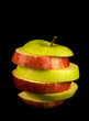 sliced red and green apple isolated on black