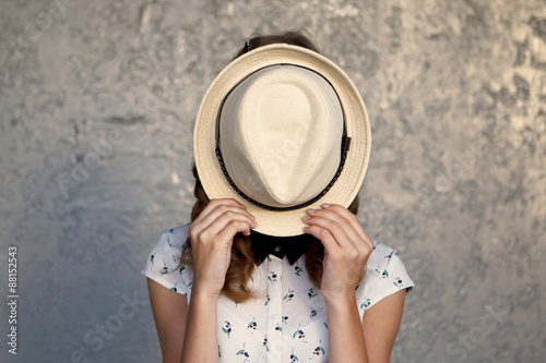 Fotografía Young girl with hat. Hides her face.Depression.