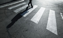 Dangerous Road Crossing With Pedestrian Feet And Shadow. Concept Safety.