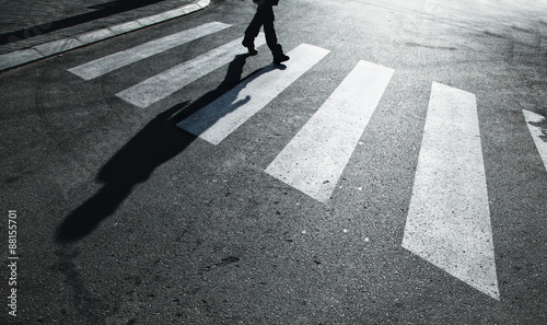 Fotografia Dangerous road crossing with pedestrian feet and shadow