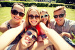 group of smiling friends making selfie in park
