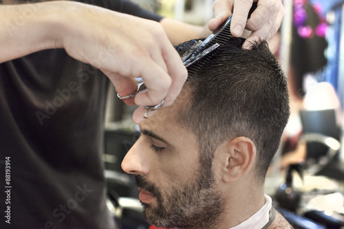 plakat Un parrucchiere mentre utilizza le forbici