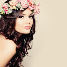Beautiful Young Woman With Summer Pink Flowers. Long Permed Curl