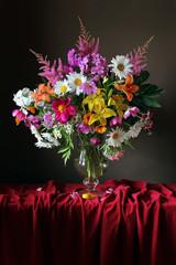 Obraz na PlexiБукет из садовых цветов в кувшине на красной скатерти