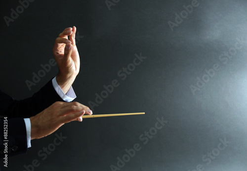 Fotografiet  Music conductor hands with baton on black background