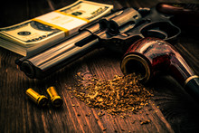 Money And A Gun With A Pipe On A Wooden Table