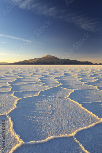 An Andean volcano rises above the Salar de Uyuni, the incredible salt desert, during a summer sunset, Oruro, Bolivia, South America #88320952