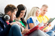 Group of students on a break. Focus on a girl reading a textbook. Background is blurry.