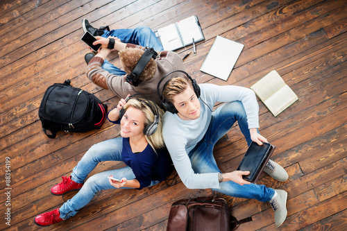 Fotografía  Group of students using smartphones and tablet in headphones listening to the music and leaning on each other on wooden floor having notebooks and bags around them