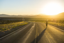 Woman Walking Down A Long Winding Road At Sunset In Eastern Nevada