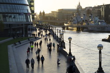 Pedestrians Silhouetted On More Place Riverfront With City Hall And HMS Belfast Behind, London