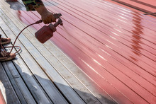 Spray Red Color To Paint The Steel Of A Building
