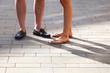 canvas print picture - Beine eines sommerlich gekleideten Paares in der Stadt