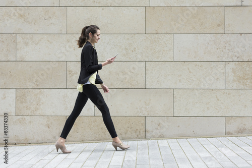 Foto  Businesswoman looking at phone while walking.