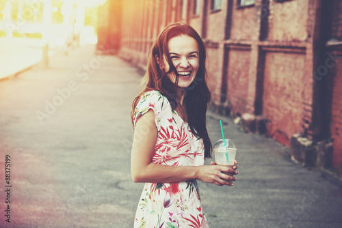 Poster de jardin Lait, Milk-shake pretty laughing girl with milk shake walking at morning street