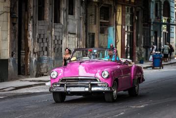 Kuba pinker amerikanischer Oldtimer fährt auf der Strasse in Havanna Stadt