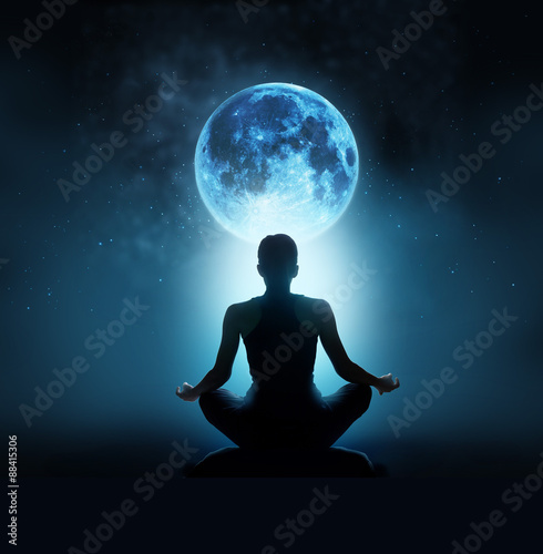 Fényképezés  Abstract woman are meditating at blue full moon with star in dark background