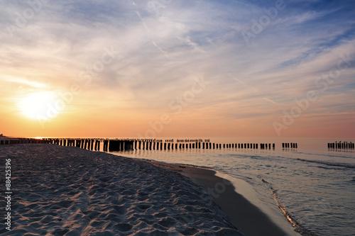 Fototapeta Zachód słońca i falochrony na Morzu Bałtyckim do pokoju