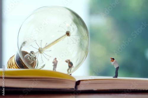 Fotografie, Obraz  Creative idea concept - miniature photographer with vintage ligh