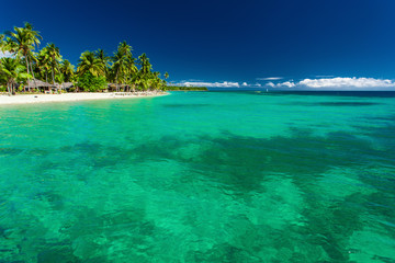 Tropical island in Fiji with beach and water with coral