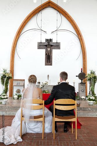 Brautpaar sitzt vor Altar und wartet auf Trauung Wall mural