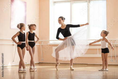Fényképezés  Young girl warming up and talking to younger classmates at ballet dancing class
