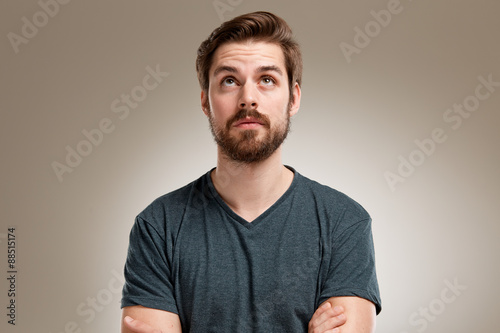 Fotografering  Portrait of young man with beard, looking up straight