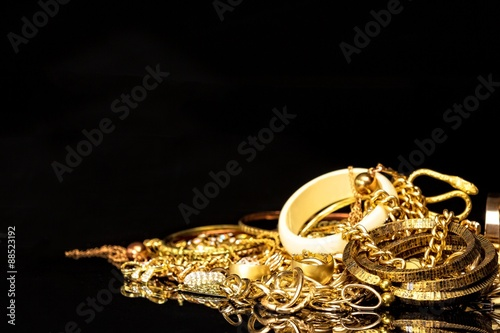 Pinturas sobre lienzo  Bunch of gold jewelry against black background with copy space for text