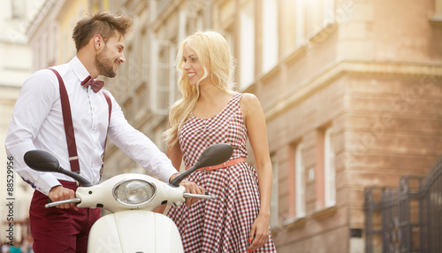Love couple on the street with retro scooter Fototapet