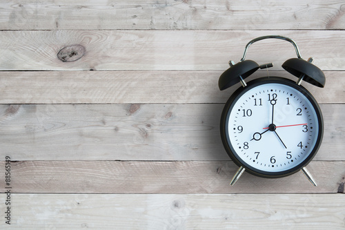 Fotografia Alarm clock isolated on wooden floor