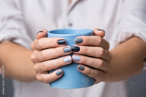 Photographie  Mains féminines avec tasse bleue