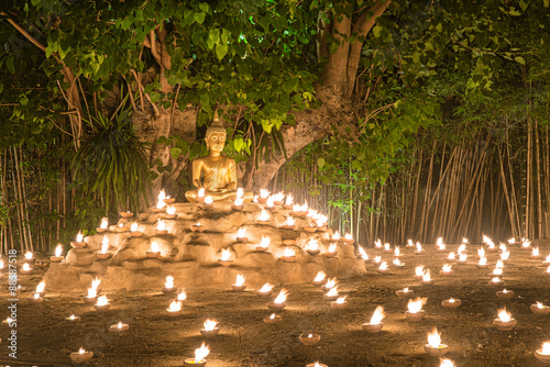 Buddhist monk fire candles to the Buddha with beautiful water reflection in Phan Tao Temple, Chiangmai, Thailand.