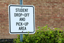Sign For Student Drop Off And Pick Up Area Against Brick School Building