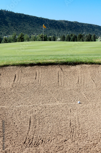 Photo  Rolling golf ball in a sand trap and yellow flag
