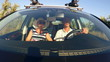 Family with children traveling by car on summer vacation singing road trip song