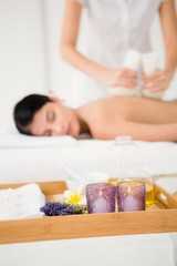 Obraz na płótnie Canvas Pretty woman enjoying a herbal compress massage