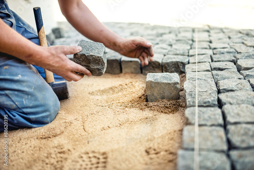 construction worker placing stone tiles in sand for pavement, terrace Wallpaper Mural