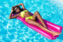 African Woman On Air Mattress In Swimming Pool