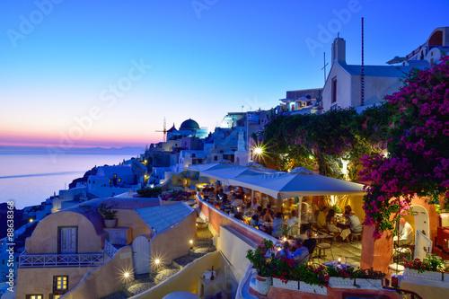 Fototapeta Dusk scene on the seaside with public terrace in evening lights in Santorini, Greece obraz