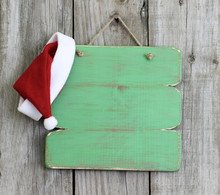 Blank Green Wood Christmas Sign With Santa Claus Hat Hanging On Rustic Door