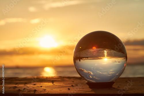 Fotografie, Obraz Die Sonne geht über dem Bodensee unter und leuchtet durch eine Glaskugel