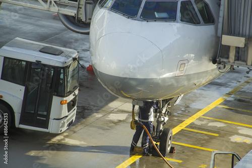 Türaufkleber Flugzeug Ground crew refueling and working below a passenger airplane.