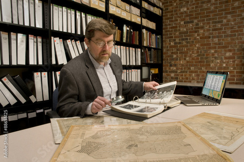 Researcher in archive, searching through maps and photographs Wallpaper Mural