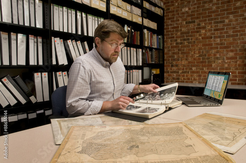 Photo Researcher in Archive Examining Maps and Other Archival Material